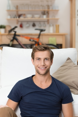 Portrait of a handsome unshaven young man sitting on a sofa in the living room looking at the camera with a beaming smile photo