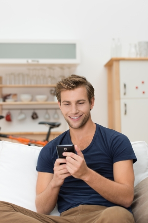 Handsome casual young man sitting on a sofa at home reading an sms on his mobile phone with a smile photo