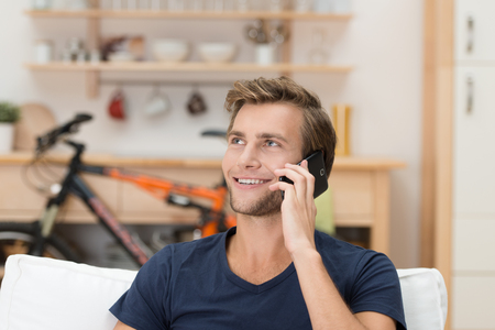 calling on phone: Handsome casual young man with a friendly smile talking on a mobile phone sitting in his living room Stock Photo