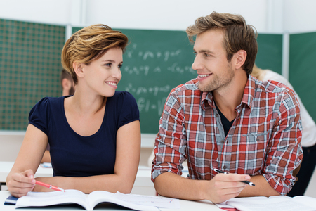 flirting: Attractive young male and female college students sharing a desk together sit in the classroom discussing a project and smiling at each other Stock Photo