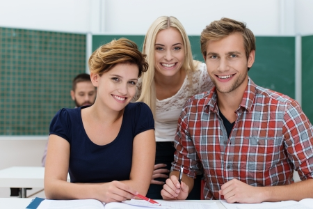 Smiling university students, an attractive young man and two women, working together as a team in the classroom sitting giving the camera warm friendly smiles Stock Photo - 22250096