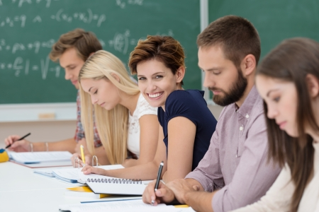 turning table: Smiling beautiful young woman in the classroom sitting in a line of students working together at a long table, turning to smile at the camera Stock Photo