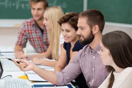 erwachsene: Diverse Gruppe von attraktiven jungen Studenten studieren zusammen an einem Tisch sitzen sich einen Computer-Monitor