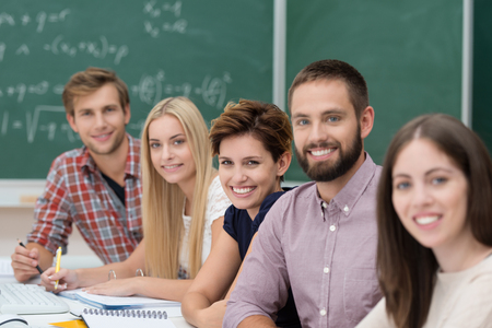 Group of happy successful university students sitting together at a table in the classroom working and studying smiling at the camera Stock Photo - 22250112
