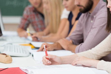 Group of people in a meeting or class sitting at a long table together concentrating on paperwork in front of them, close up view of their arms Stock Photo - 22250114