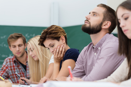 Young thoughtful male university student sitting in a group of students busy studying at a table with his head tilted back as he tries to solve a problem or seek inspiration photo