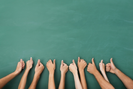 gestures: Close up view of the hands of a group of people giving a thumbs up gesture of approval an success with their hands raised against a blank green chalkboard with copyspace