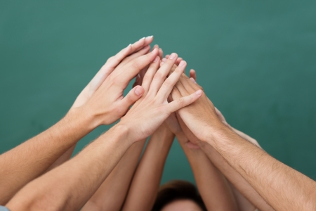 Teamwork and cooperation with a group of young people all raising their hands together and forming an overlapping pyramid, closeup view of their arms and hands