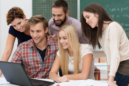 outcome: Successful team of diverse young male and female students in the classroom smiling with delight as they read the outcome of their project on a laptop computer