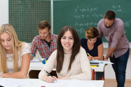 Pretty young female college student sitting at her desk working in the classroom with her peers Stock Photo - 22250147
