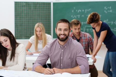 Happy successful young bearded male student sitting at his desk in a classroom with his fellow students giving the camera a beaming smile Stock Photo - 22250150