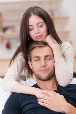 living moment: Romantic young couple sharing a loving moment in their living room sitting in an intimate embrace with their eyes closed in bliss