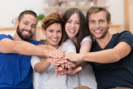 integrated groups: Teamwork amongst friends with a laughing enthusiastic group of young people stacking their hands together with focus to the hands