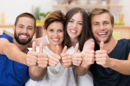 solidaridad: Atractivo grupo de jóvenes felices y mujeres que dan un pulgar hacia arriba gesto de aprobación y el éxito con el foco en las manos