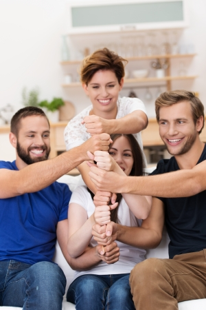 integrate: Happy laughing young men and women making a tower stack of their hands and fists in a team effort of cooperation