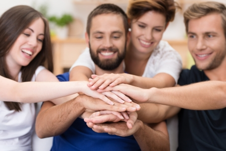 Group of happy smiling young friends stacking hands in a joint effort of cooperation and teamwork with focus to their hands