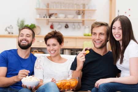 watching movie: Frontal view of a laughing group of diverse young friends sitting on a sofa watching television and eating snacks