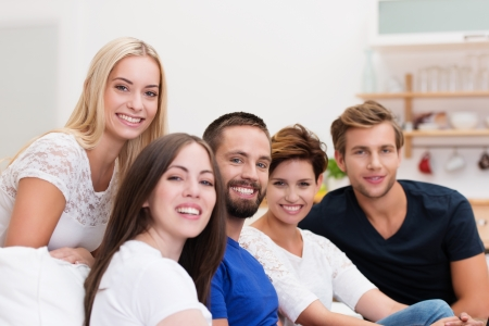 Group of young men and women relaxing at home on a living room sofa turning to smile at the camera with focus to a bearded young man in the centre photo