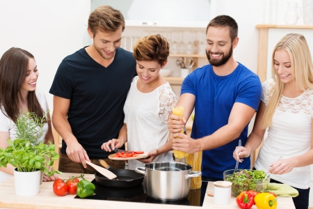 Group of diverse young friends preparing dinner together in the kitchen standing at the counter and hob cooking spaghetti and salads