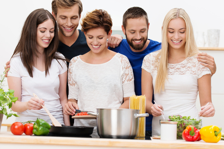 Group of beautiful young women cooking spaghetti and salads in the kitchen with their husbands watching over their shoulders as they pose as a group at the hob photo