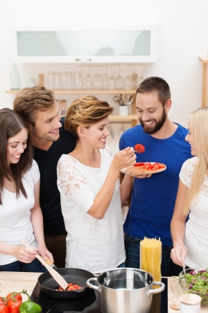 as one: Diverse group of young friends cooking dinner together in the kitchen laughing as one man is tempted to try the recipe by a young woman