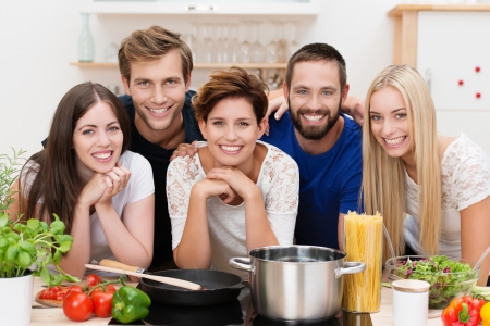 Group of diverse young people posing together in the kitchen while preparing pasta with an array of fresh ingredients and spaghetti in front of them as they smile at the camera Stock Photo
