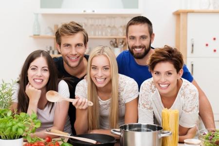 mujeres cocinando: Sonriendo grupo multicultural de j�venes hombres y mujeres que cocinan en la cocina que se presenta con sus ingredientes alrededor de la estufa