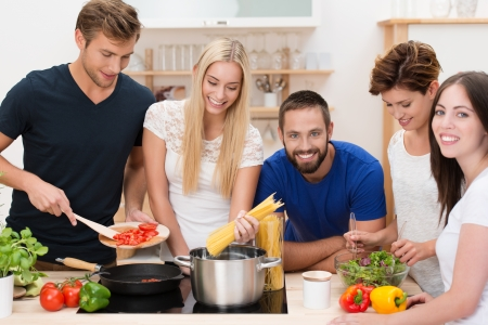 Group of diverse young friends preparing pasta standing around the stove cooking spaghetti and a tomato based sauce