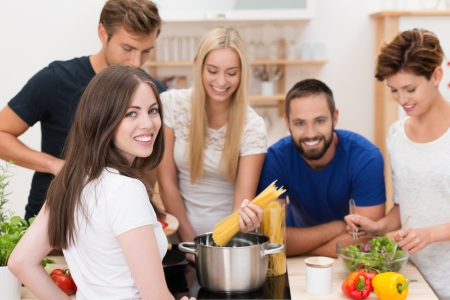 Teamwork in the kitchen with a group of happy young men and women gathered around a stove cooking spaghetti and salads photo