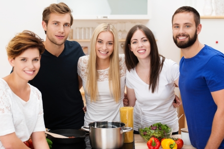 Group of happy young friends preparing lunch standing smiling at the camera grouped around the stainess steel pot and fresh healthy ingredients photo