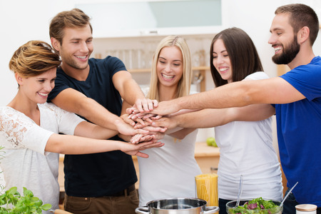 Group of enthusiastic multicultural young friends with happy smiles standing in the kitchen placing their hands in a stack denoting cooperation and teamwork photo