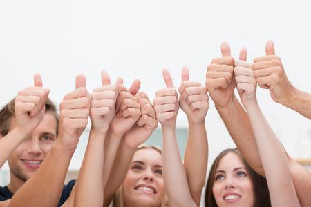 Grupo de jóvenes hombres de negocios diversos que dan un pulgar hacia arriba de pie con sus brazos levantados en el aire para indicar su éxito y aprobación