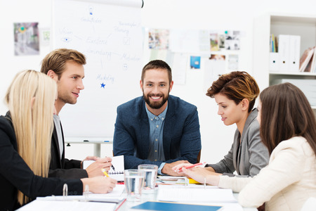startup: Group of business people in a meeting seated grouped around a table having a discussion with focus to a smiling man at the head of the table