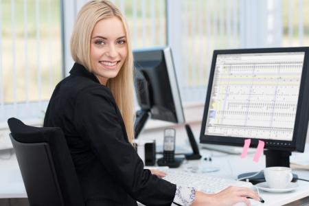 Glimlachende vertrouwen jonge zakenvrouw zit aan haar bureau in de voorkant van een desktop computer draaien om te glimlachen naar de camera