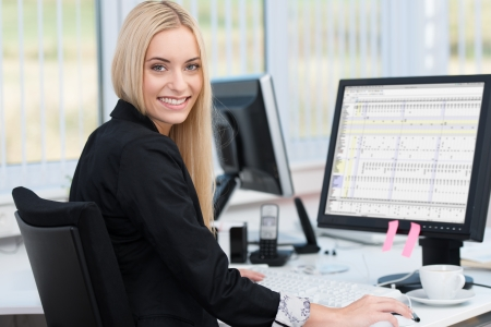 front desk: Smiling confident young business woman sitting at her desk in front of a desktop computer turning to smile at the camera