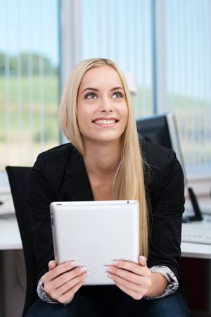 Smiling businesswoman sitting thinking with a tablet computer in her hands as she anticipates a successful outcome photo