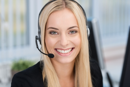 Lachende jonge vrouw draagt een hoofdtelefoon beantwoorden van oproepen op een client service center of willen de handen vrij te communiceren terwijl ze blijven werken in haar kantoor Stockfoto