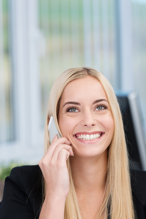 20s  closeup: Beautiful happy woman listening to a conversation on her mobile phone looking up into the air with a beaming smile, copyspace above Stock Photo