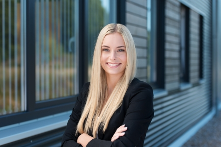 Happy confident young businesswoman standing outside her office building with folded arms smiling at the camera Zdjęcie Seryjne