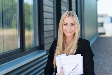 clasping: Smiling attractive young businesswoman standing outside the office building clasping paperwork to her chest and looking at the camera