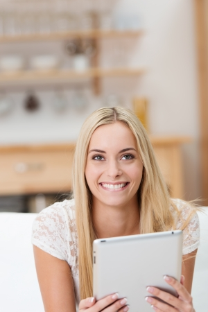 Beautiful young woman with a notepad or tablet computer in her hands looking up to smile at the camera as she sits on a sofa in the living room photo