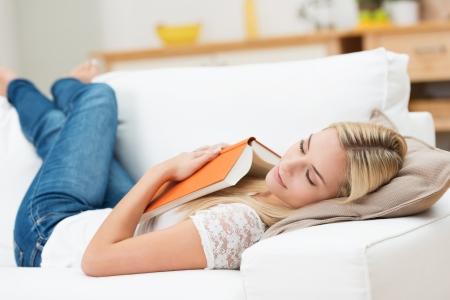 cansancio: Mujer joven cansada de tomar una siesta en casa acostado en un sof� con un libro que estaba sobre el pecho y los ojos cerrados