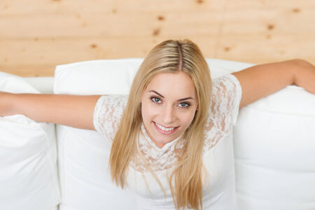 Smiling beautiful young blond woman sitting on a sofa looking up at the camera with a charming smile, high angle view Stock Photo - 22729007