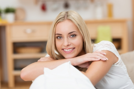 Beautiful friendly young woman with a lovely smile resting her arms and chin on the top of a sofa looking at the camera photo
