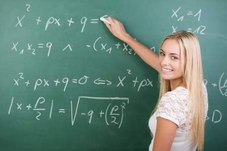 algebra: Clever confident female student in the classroom writing on a chalkboard completing mathematical equations Stock Photo