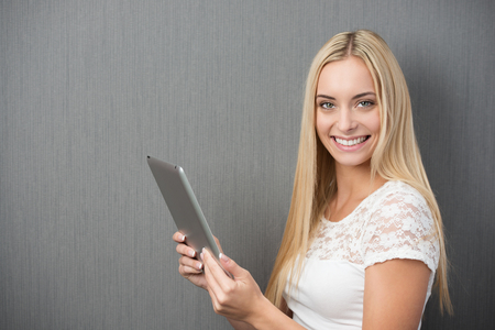 Happy beautiful woman with a tablet-pc in her hands turning to smile at the camera while standing in front of a green background with copyspace photo
