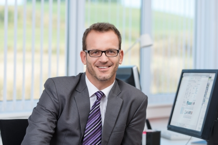 Hombre de negocios cómodo con gafas sentado en su escritorio en la oficina mirando a la cámara con una sonrisa Foto de archivo - 22729019