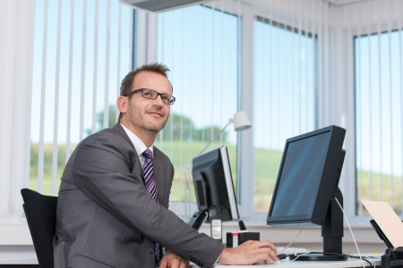 Businessman sitting at his desk in the office thinking and planning a business strategy with a large view window overlooking countryside behind him photo