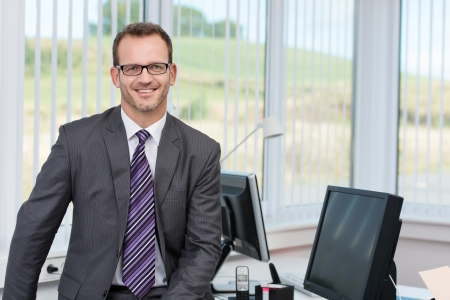 financial executive: Confident successful male business executive relaxing on the edge of his desk in front of a view window overlooking countryside