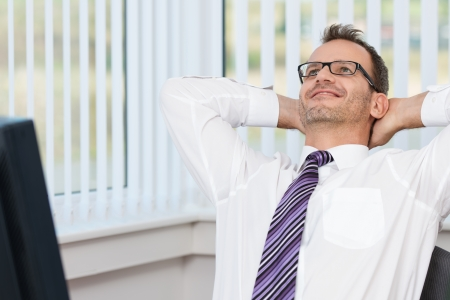 Businessman relaxing at his desk leaning back in his chair with his hands behind his head and a contented smile photo